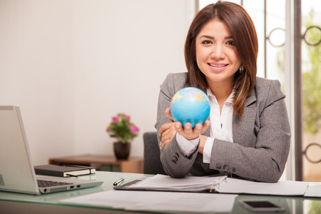 convey: Portrait of a pretty mixed-race business woman holding a small globe to convey she works for an international company Stock Photo