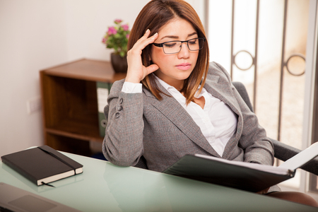 Young Hispanic business woman wearing glasses focused on her work while sitting in her office