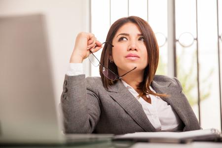 women thinking: Retrato de una bella mujer de negocios de raza mixta mirando y so�ando despierto en su oficina Foto de archivo