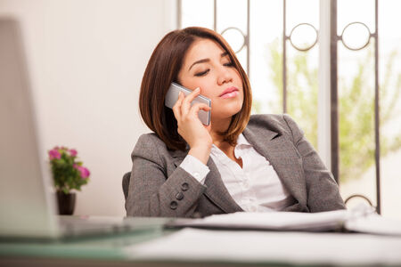 important phone call: Cute young business woman during an important call from work on her cell phone