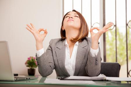 personas trabajando en oficina: Mujer de negocios joven tensionada haciendo algunos ejercicios de respiraci�n y meditaci�n en su oficina