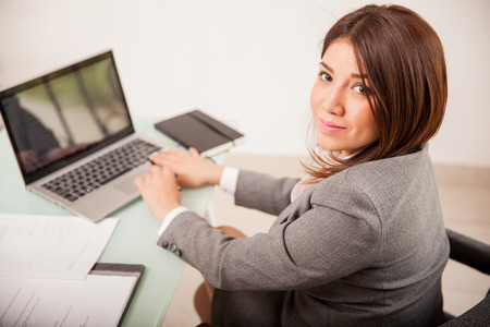 laptop: Pretty mixed-raced young business woman using a laptop computer for work