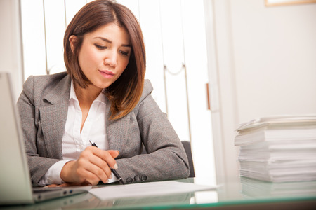 Beautiful young lawyer reviewing and signing a lot of documents at work