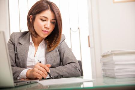 Mooie jonge advocaat herzien en het ondertekenen van een heleboel documenten op het werk Stockfoto