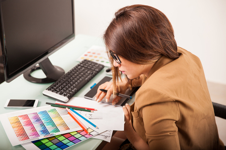 Profile view of a pretty female designer looking at some color swatches at work Stock Photo