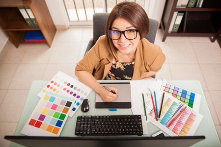 Top view of a cool looking female designer enjoying her job and smiling
