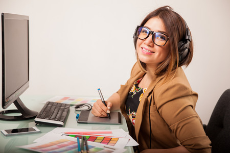 Portrait of a beautiful graphic designer using a pen tablet and listening to music