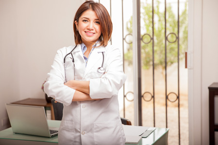 nutritionist: Cute young female nutritionist in a lab coat standing next to her desk in an office and smiling Stock Photo