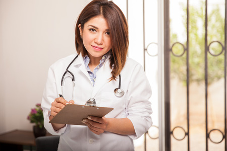 Cute female doctor in a lab coat reviewing a patient photo