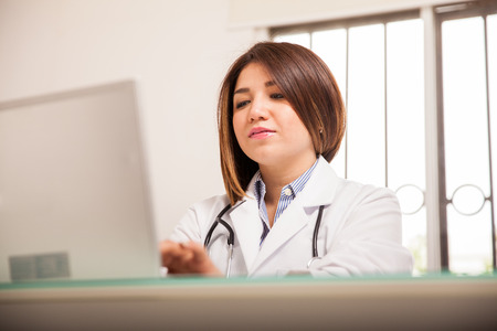Beautiful young doctor in a lab coat working on a laptop computer in her office photo