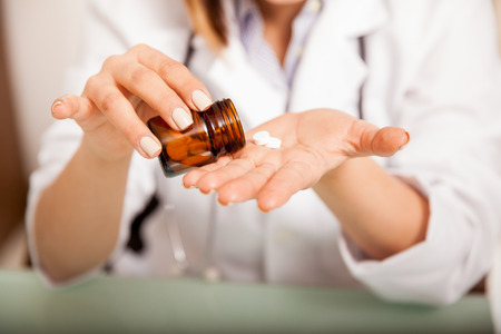 nutritionist: Closeup of a female doctor pouring some meds from a bottle on her hand