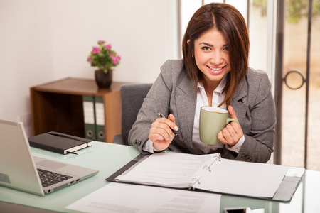 Beautiful Hispanic business woman working at her office and having a cup of coffee photo