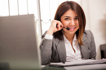 customer service representative: Pretty Latin sales representantive wearing a headset and smiling at her office