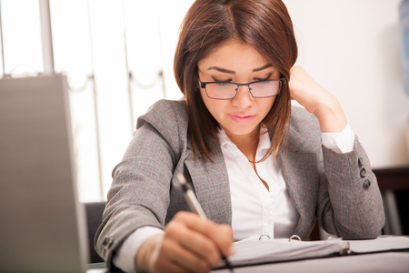 Pretty Hispanic young business woman taking some notes and working in her office Imagens