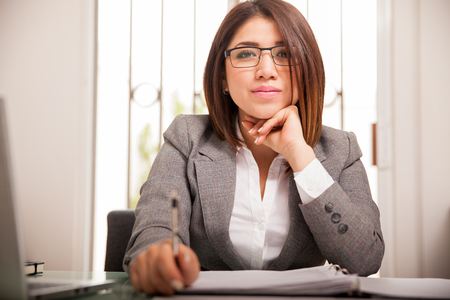 front desk: Portrait of a confident young business woman sitting in front of her desk and looking serious Stock Photo