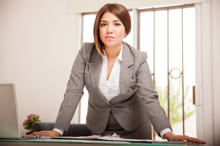 Successful and confident Latin business woman leaning on her desk and looking all serious Stock Photo