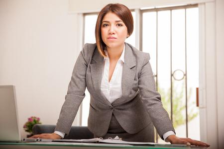 Succesvol en zelfverzekerd Latijns-zakenvrouw leunend op haar bureau en kijkt alle ernstige