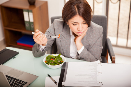 office desk: Busy young business woman eating a healthy lunch while working in her office Stock Photo
