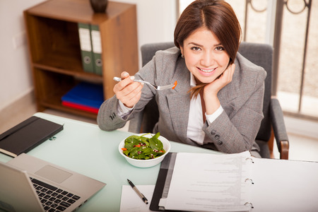 Happy Hispanic business woman eating a salad from a bowl in her office while she works