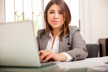 Beautiful young Latin lawyer doing some work on a laptop computer