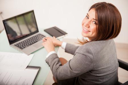 Bonne jeune femme d'affaires travaillant sur certains documents sur son ordinateur portable Banque d'images