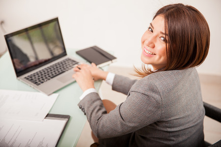woman from behind: Happy young business woman working on some documents on her laptop computer