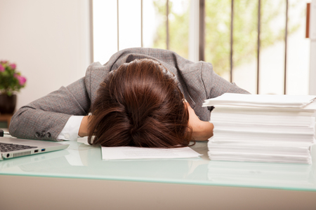 too many: Business woman just gave up on her deadline of too many documents to review at work