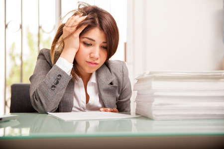 too much work: Very unhappy and overwhelmed business woman with too much work to do at her office Stock Photo