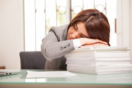 long hours: Cute young business woman falling asleep at the office after long hours of work Stock Photo