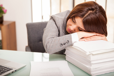 too much work: Pretty young business woman taking a nap after too much work at the office