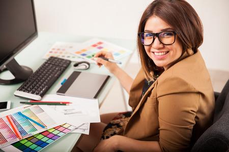 designer: Cheerful female freelance designer doing some work and smiling Stock Photo