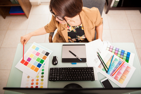 デスクトップ コンピューター上で動作し、いくつかの色の見本を使用して若いグラフィック デザイナーのトップ ビュー 写真素材