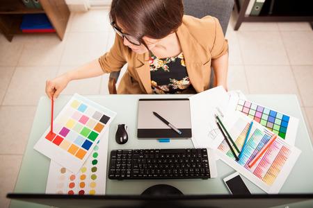 Bovenaanzicht van een jonge grafisch ontwerper werkt op een desktop computer en met behulp van enkele kleurstalen Stockfoto