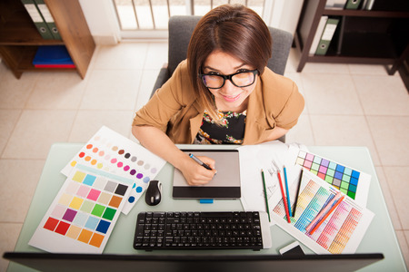 designer: Pretty mixed-raced female designer using a pen tablet and some color swatches for work
