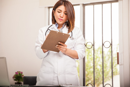 Attractive female mixed-race doctor writing some medical records at her office photo