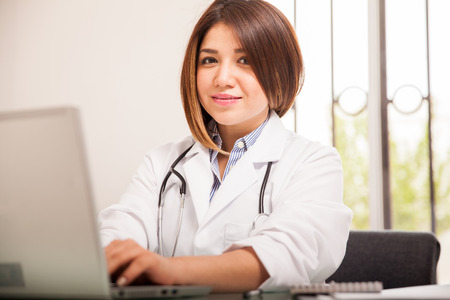 nutritionist: Attractive female Hispanic doctor using a laptop computer at her office and smiling Stock Photo
