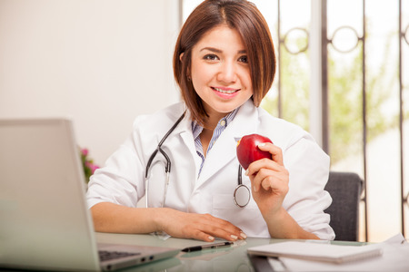 healthcare office: Cute young nutritionist in a lab coat holding an apple in her hand and smiling Stock Photo