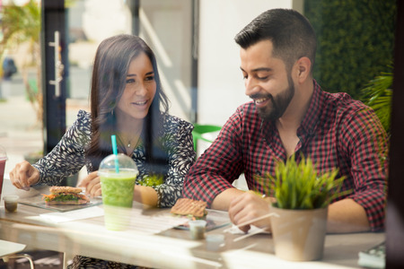 Attractive young Hispanic couple having a sandwich and a smoothie for lunch photo