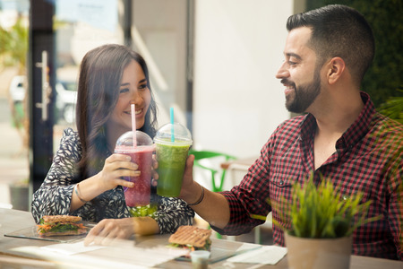 cheers: Pretty Hispanic couple enjoying their healthy smoothies and sandwiches for lunch