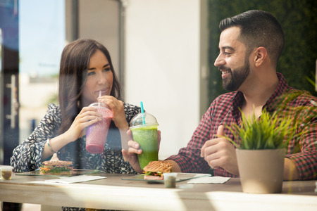 Cute Latin couple drinking smoothies and eating sandwiches during a date