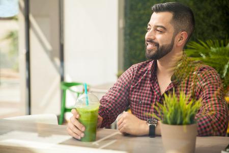 tomando jugo: Retrato de un hombre hermoso joven que disfruta de un batido saludable en un restaurante