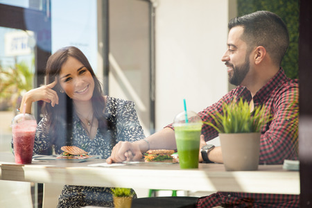 Beautiful young woman having a healthy lunch with her boyfriend and holding hands photo