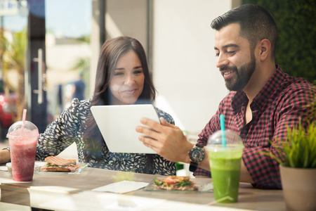 Young attractive couple using a tablet computer while eating a healthy lunch at a cafe photo