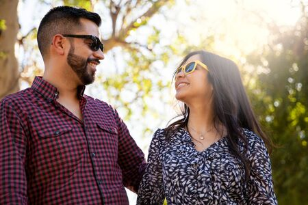 Good looking young couple having fun outdoors and wearing sunglasses Imagens