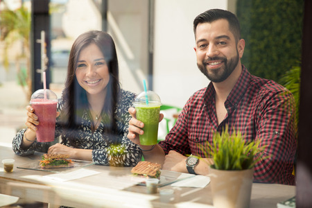 Happy young couple enjoying their healthy smoothies and sandwiches during lunch photo