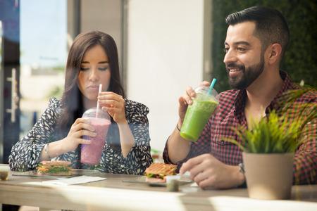 tomando jugo: Pareja joven linda que consigue que se conocen entre s� durante un almuerzo saludable