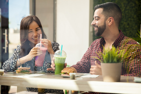 jugo de frutas: Alegre joven pareja almorzando y batidos saludables en un bar de zumos
