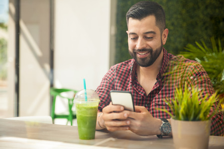 smartphone: Portrait of a happy young man using a smartphone while drinking a healthy smoothie