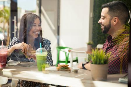 barra: Amigos hispanos j�venes atractivas que tienen s�ndwiches y batidos para el almuerzo Foto de archivo