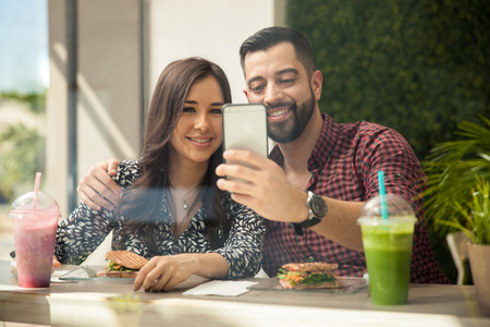 Attractive young Hispanic couple taking a selfie with a smartphone while eating lunch photo